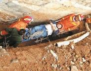 武汉一工人不慎坠入4米深坑 消防员用担架抬出